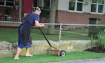 Amish woman mowing her lawn.